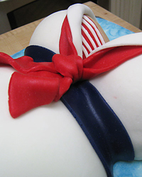 Red tie, white collar and blue sash on Nautical Baby Belly Cake