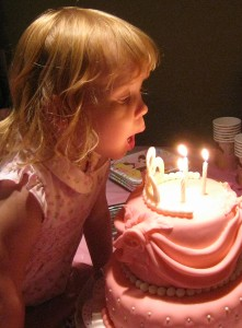 blowing out the candles princess birthday cake.
